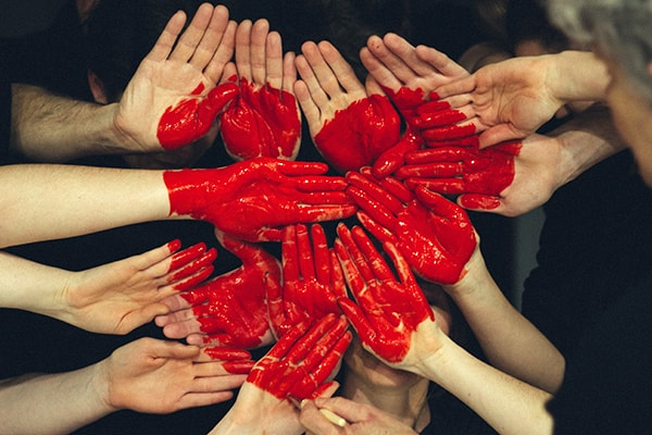 Lots of hands together painted red with heart shape. GIVE BUTTON